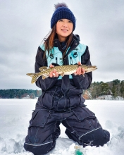 Woman holding fish caught while ice fishing