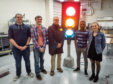 Students gather around a traffic light in an engineering class.