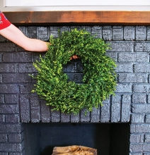 A fireplace with a wreath hanging above it.