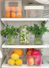 Plastic containers filled with food sit on the shelves of a well-organized fridge.