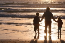 A mother holds hands with her children on a beach.