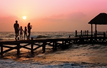 A family enjoys a sunset on the beach on their family vacation.