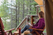 A woman reads a copy of Of Bears and Ballots at a cabin.