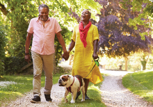 Two senior citizens walk with their pet dog.