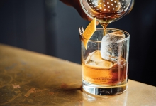 A bartender pours and old fashioned into a glass.
