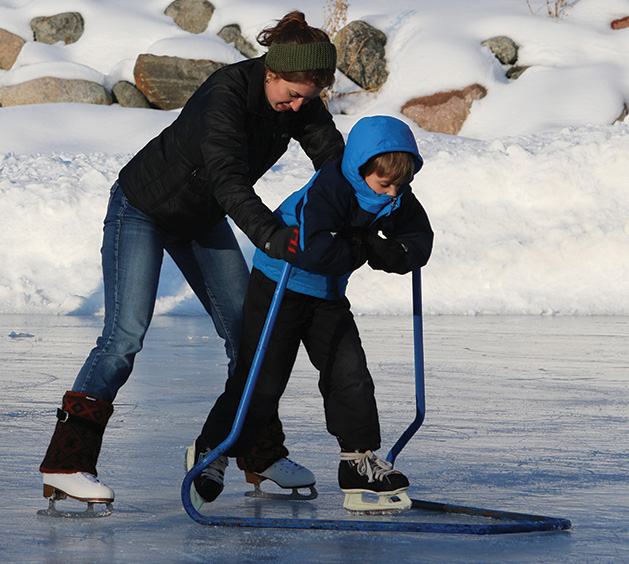 A child learning to ice skate at Centennial Lakes Park in Edina