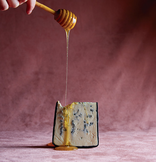 Someone drips honey onto a chunk of cheese.