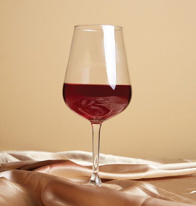 A glass of wine on a gold satin sheet