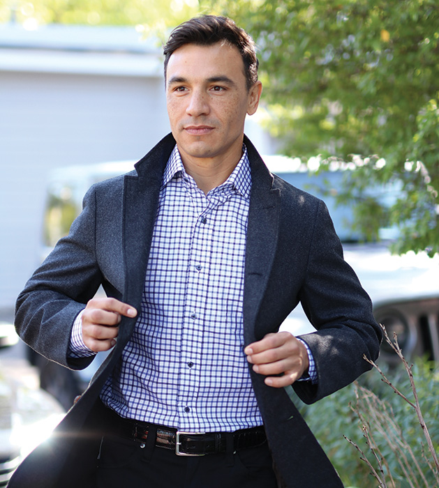 A man models a charcoal sport blazer, brown and navy dress shirt and black wool pants from CircleRock