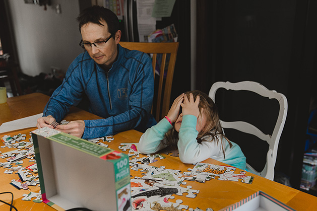 A dad and his daughter work on a puzzle together.