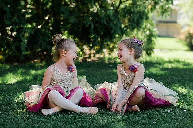 Two young ballerinas sit in the grass, laughing.