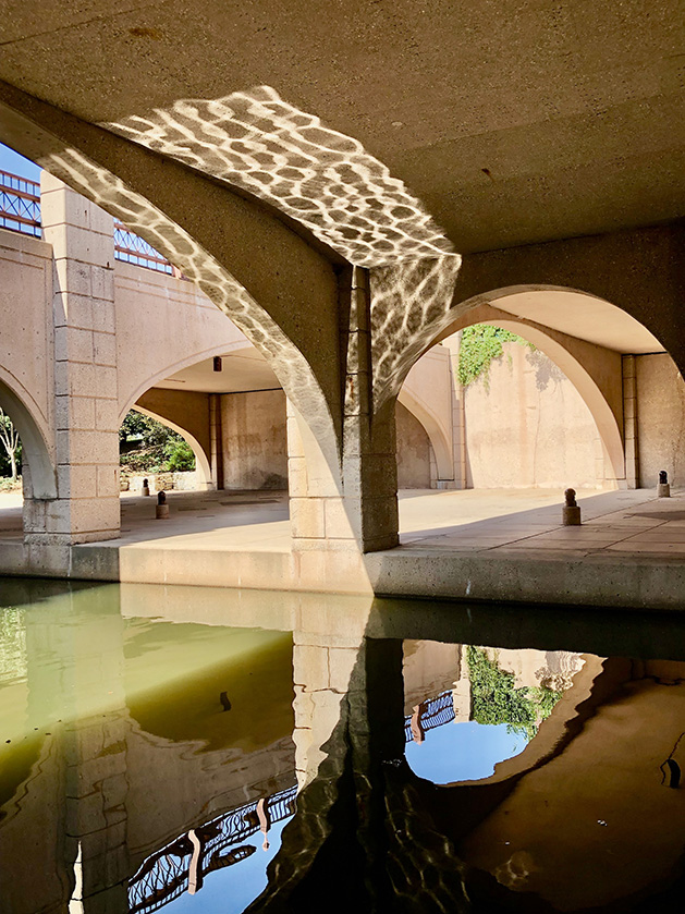 The arches under a bridge are reflected in the water at Centennial Lakes Park.