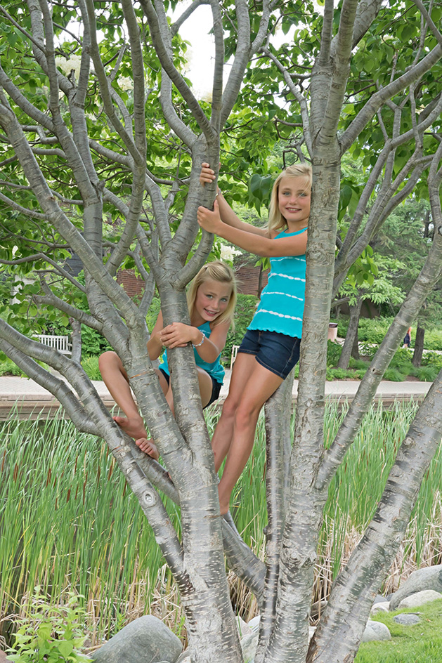 Two girls pose while climbing a tree.