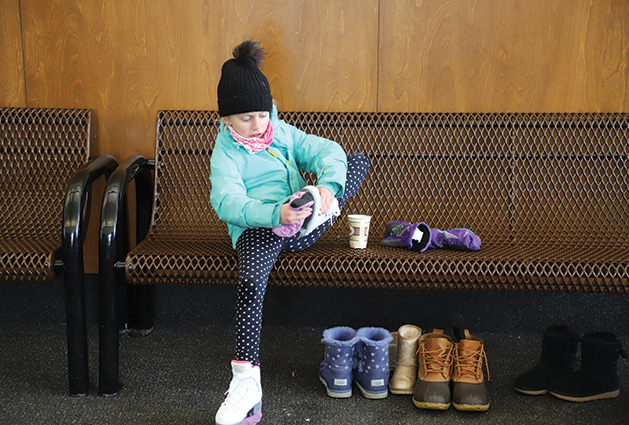 A child puts on skates at the Pamela Park warming house.