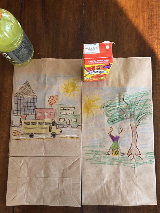 Lunch bag art depicting a school bus on the road and a kid doing a handstand